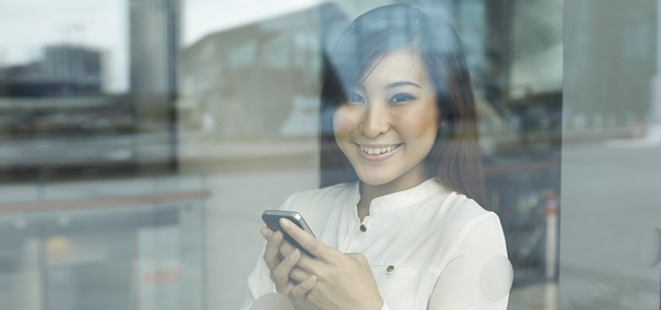 Asian Business woman using a smartphone and looking out window